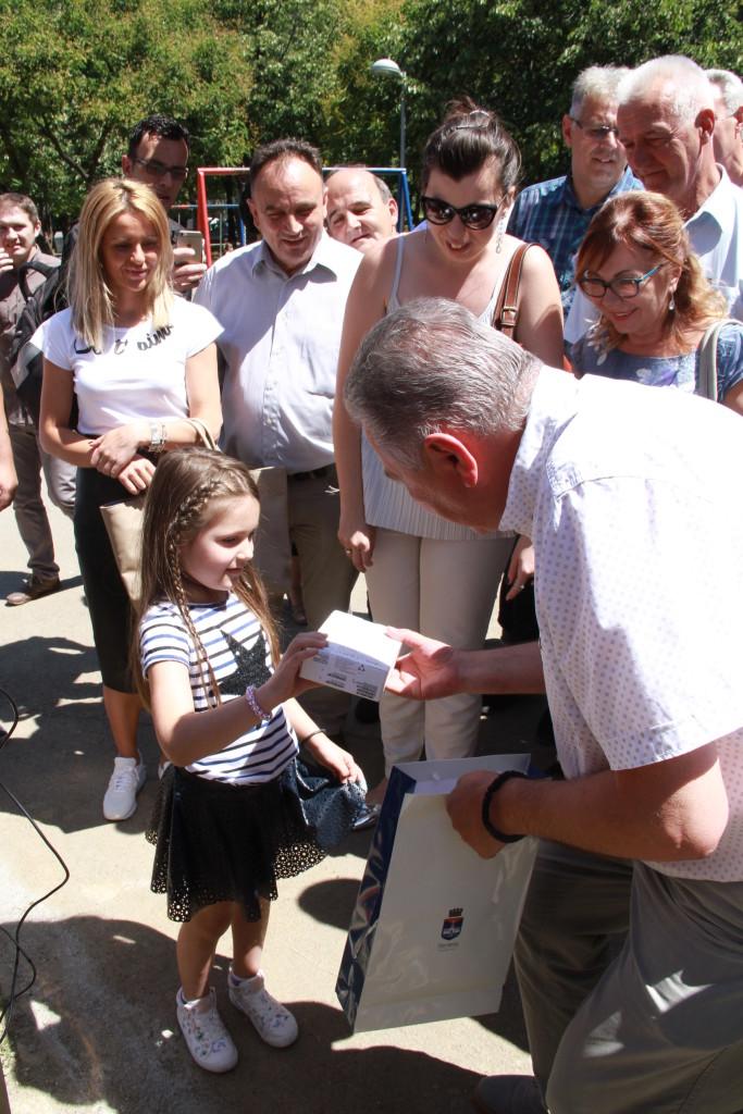 Predsednik GO Rakovica urucuje tablet devojcici